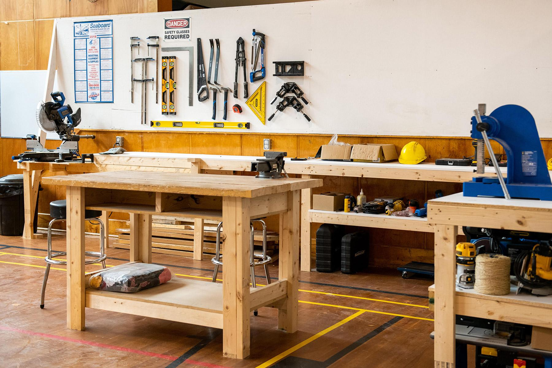 A workshop with tools and big wooden counters.