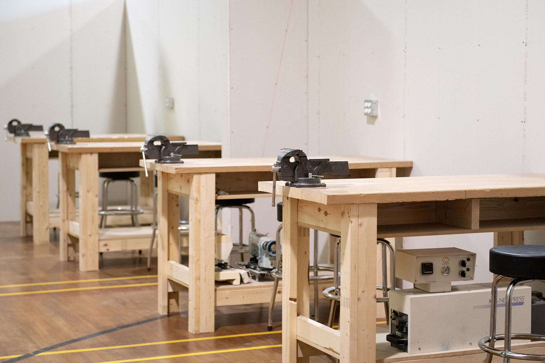 Four wooden bandsaw tables in a workshop.